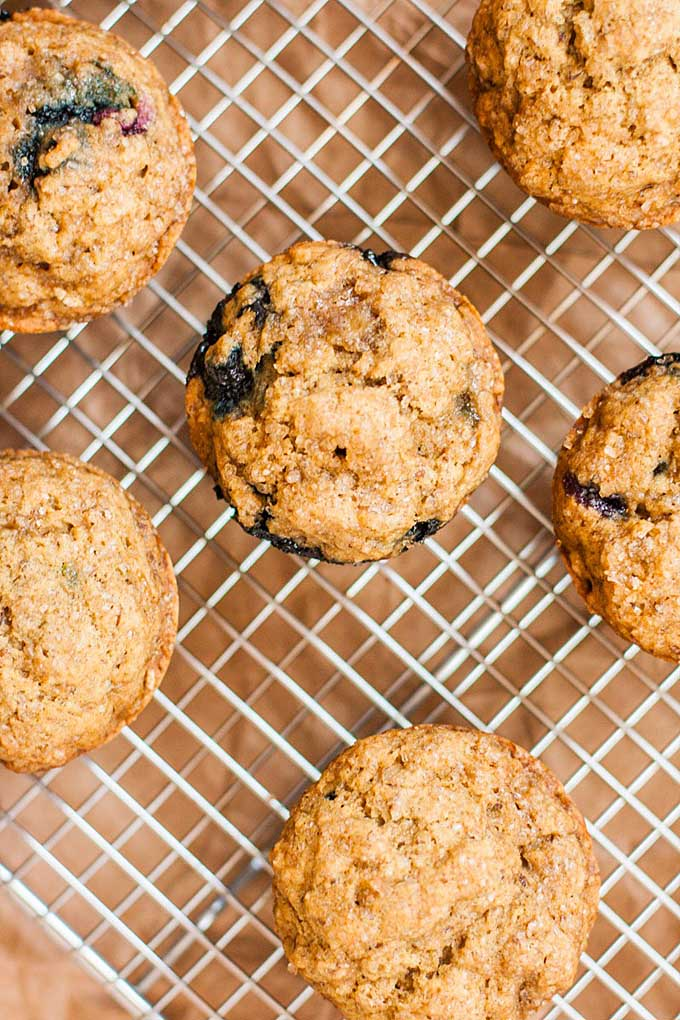 Top down vie of a batch of Whole Wheat Blueberry Banana Muffins on a cooking rack.
