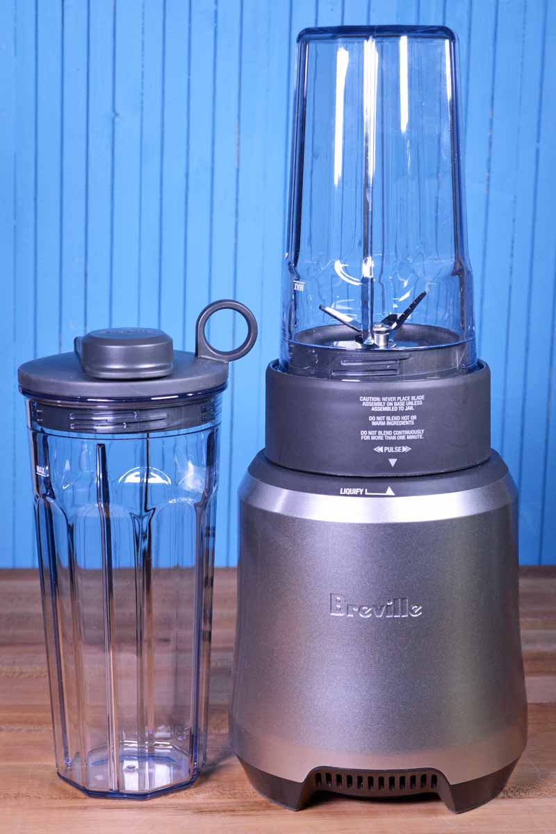 A Breville Boss To Go personal blender with an extra to-go cup on a blue background.
