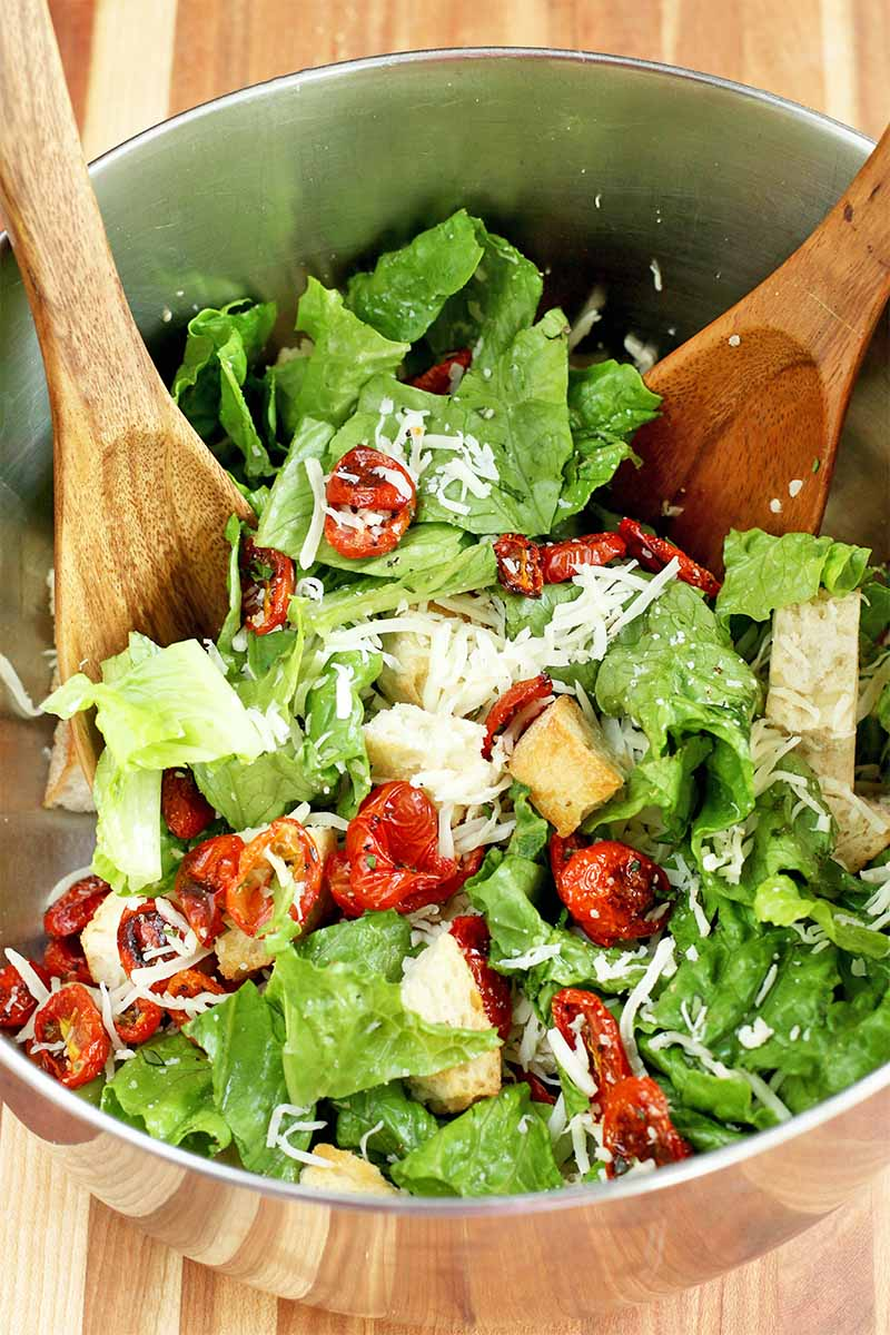 Vertical top-down image of two wooden utensils being used to toss a homemade panzanella salad.