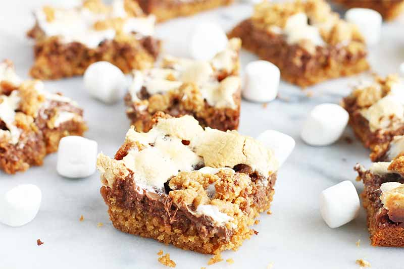 Homemade s'mores bars with a graham cracker base topped with melted milk chocolate and toasted miniature marshmallows, on a gray and white marble surface.