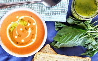 Top-down shot of a white bowl of orange tomato soup topped with a drizzle of cream and dots of green herb oil, with a jar of basil oil beside a sprig of the fresh herb, two slices of bread at the bottom of the frame, and a folded gray and white cloth napkin topped with a stainless steel spoon at the top of the frame, on a blue wrinkled cloth.
