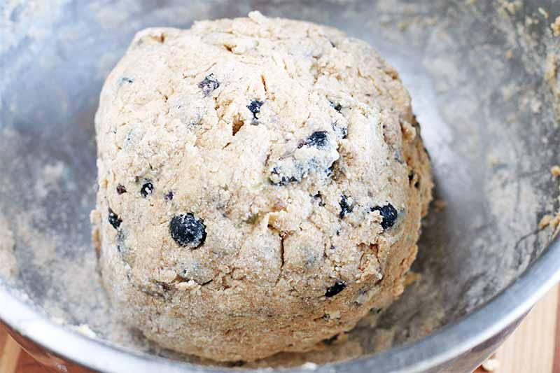 A ball of scone dough studded with blueberries, in a stainless steel mixing bowl on a brown wood table.