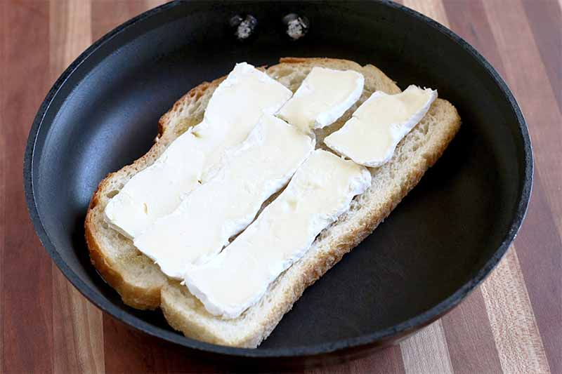 Thinly sliced pieces of brie are arranged in rows to cover the surface of a piece of sourdough bread, in a black nonstick frying pan, on a wood background.