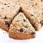 A round blueberry crumb cake with a triangular slice taken out with a cake server, on a white background with scattered berries.