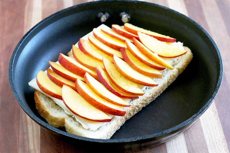 Peach slices are arranged in two rows on a piece of sourdough bread topped with cheese, in a black nonstick frying pan, on a striped wood surface.