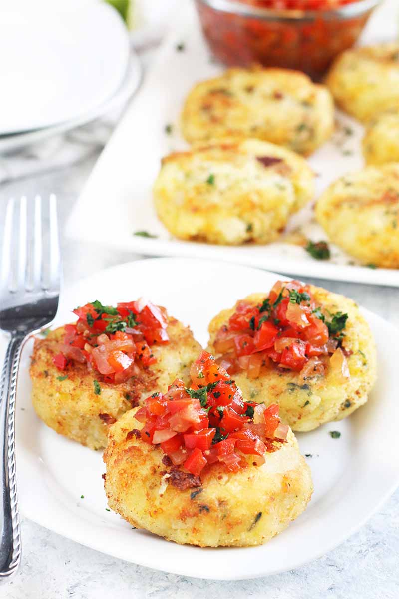 Three mashed potato fritters topped with red pepper and onion relish on a white plate with a fork, with more on a serving platter in the background.
