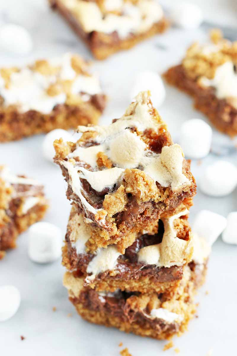 Three stacked s'mores bars in the foreground with more scattered in the background among mini marshmallows and crumbs, on a marble surface.