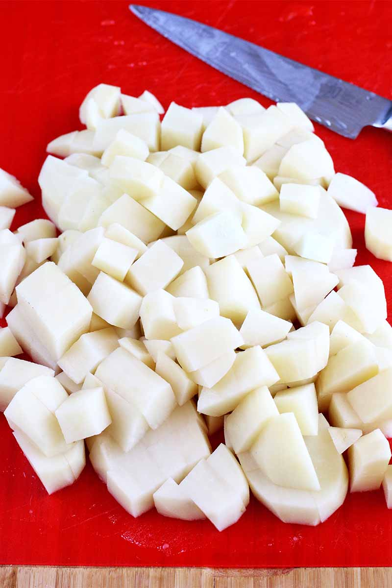 Peeled and chopped potatoes on a red cutting board with a knife.