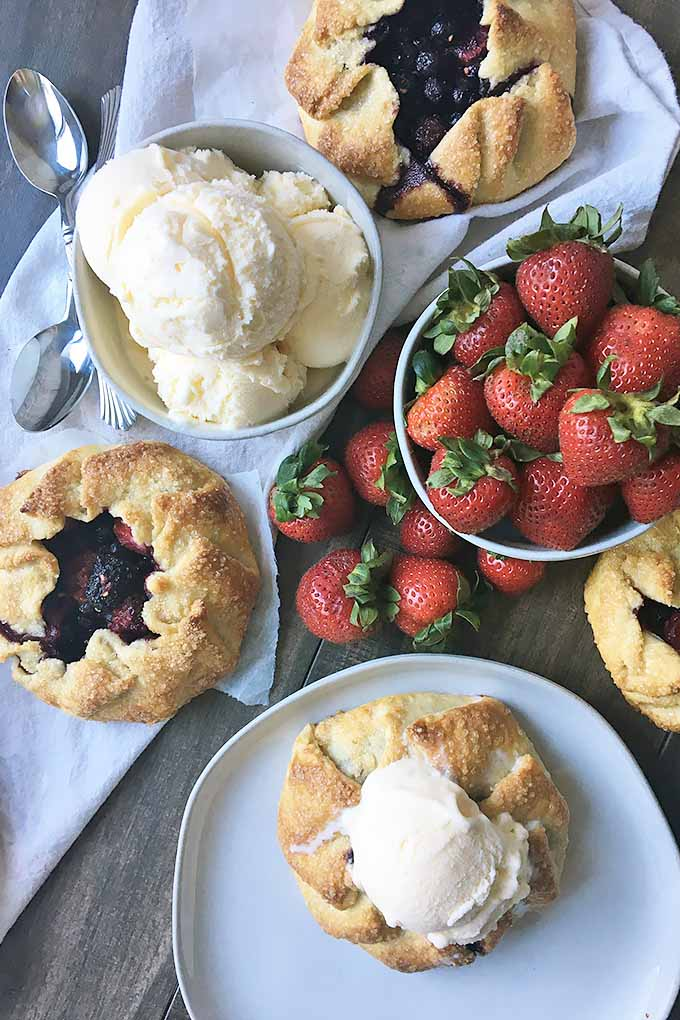 Vertical image of bowls of ice cream and strawberries next to galettes.