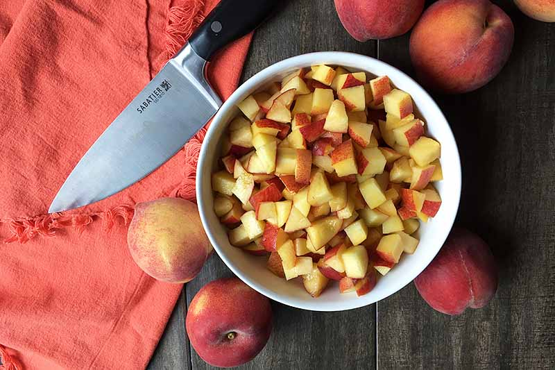 Horizontal image of a bowl of diced peaches next to a knife.