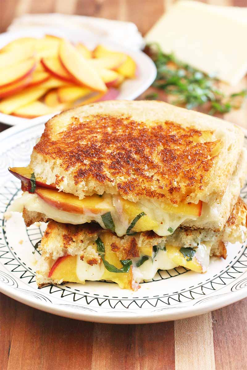 Two halves of a grilled cheese sandwich with fresh peaches and basil are stacked on a white patterned lunch plate, with another plate of fruit in the background beside more prepped ingredients, on a striped wooden cutting board.