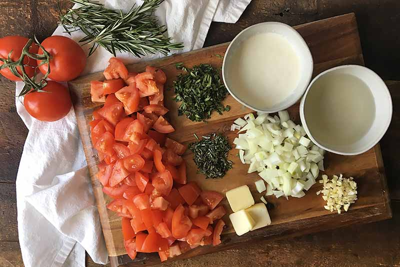 Horizontal image of prepped ingredients on a wooden cutting board for a pasta sauce.