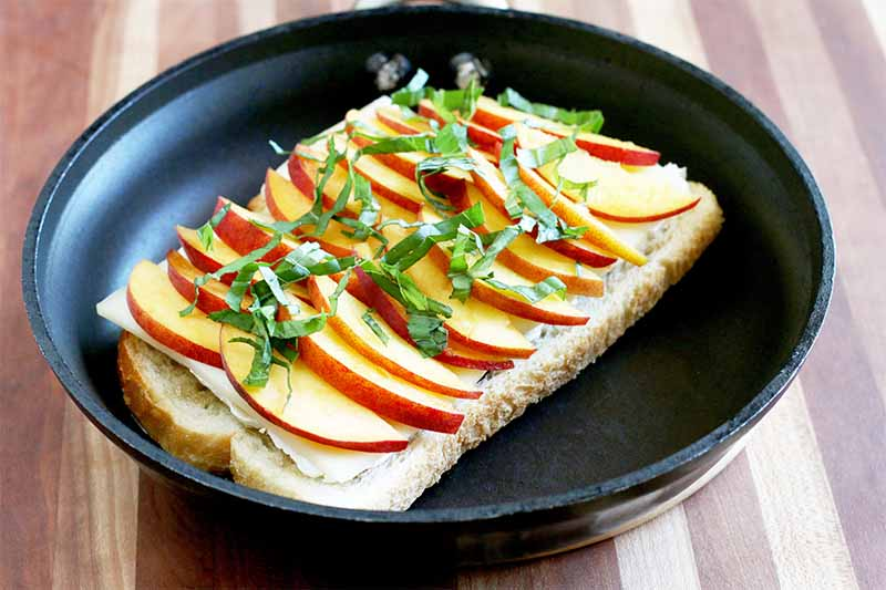 Sliced peaches with the skin on with basil chiffonade on top are arranged on a large piece of sourdough bread in a black nonstick frying pan, on a striped wooden cutting board.