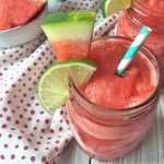 Horizontal image of watermelon daiquiris in glass jars with garnishes on a gray wooden surface with a spotted napkin.