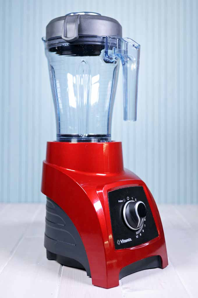 Oblique view of a red Vitamix S30 personal blender on a light blue background.