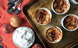 Horizontal image of ramekins with fruit cobbler on a baking sheet next to a bowl of whipped cream, peaches, and spoons on an orange towel.