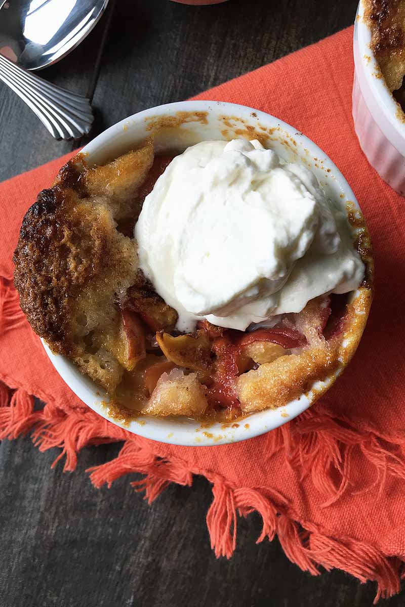 Vertical image of one peach cobbler topped with whipped cream with spoons and an orange towel.