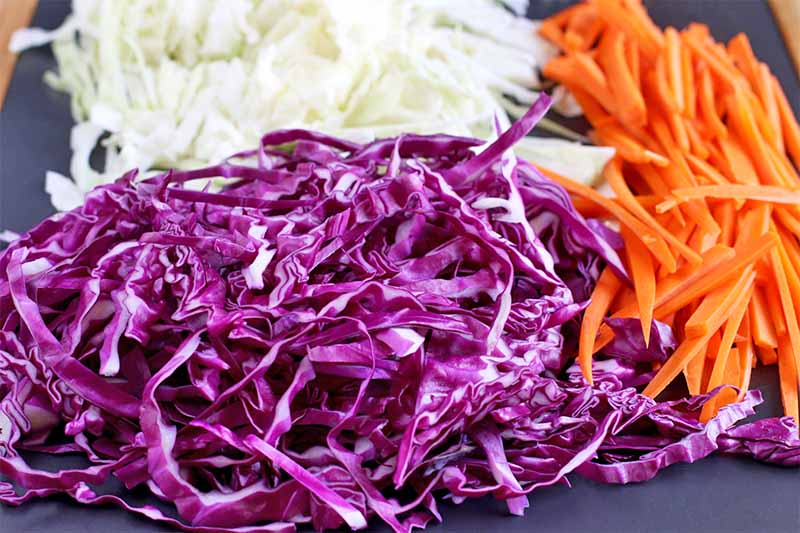 Three small piles of shredded purple and green cabbage and orange carrots, on a dark gray slate background.