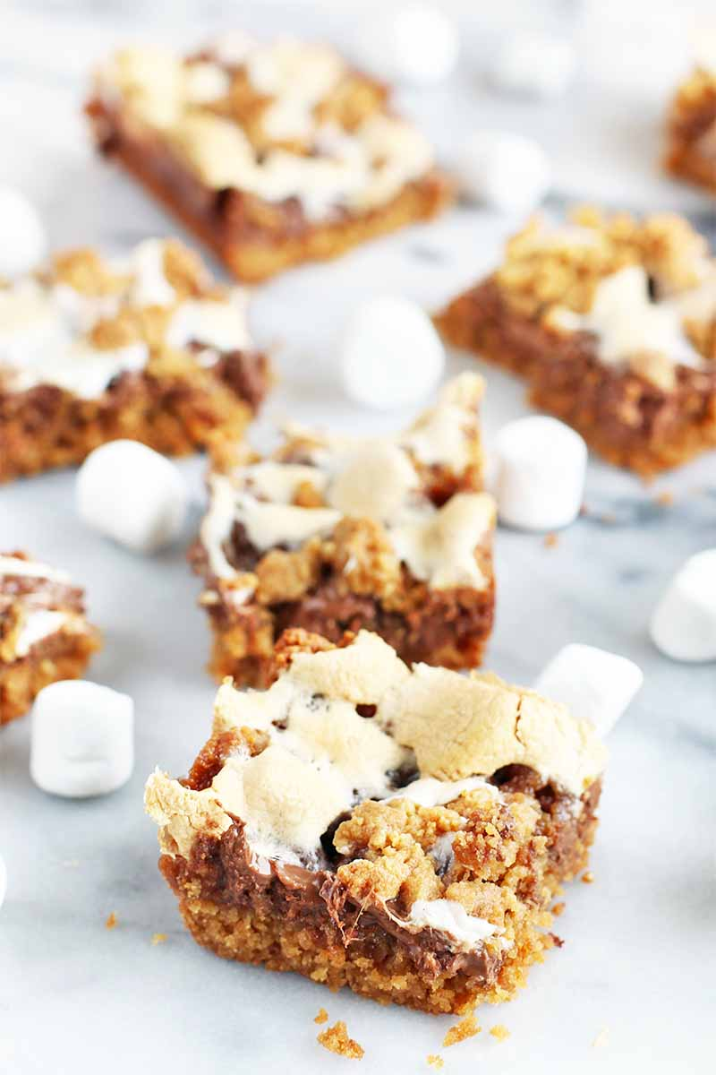 Oblique view of two graham cracker and chocolate dessert bars in the foreground with five more scattered with white miniature marshmallows on a gray marble surface in shallow focus behind them.