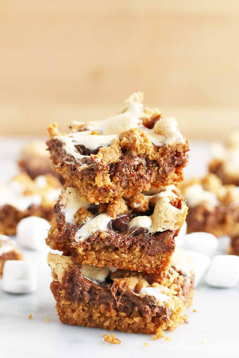 Vertical image of a stack of three graham cracker, chocolate, and marshmallow dessert bars with more of the desserts and mini marshmallows in shallow focus in the background, on a marble surface with a beige wall behind it.