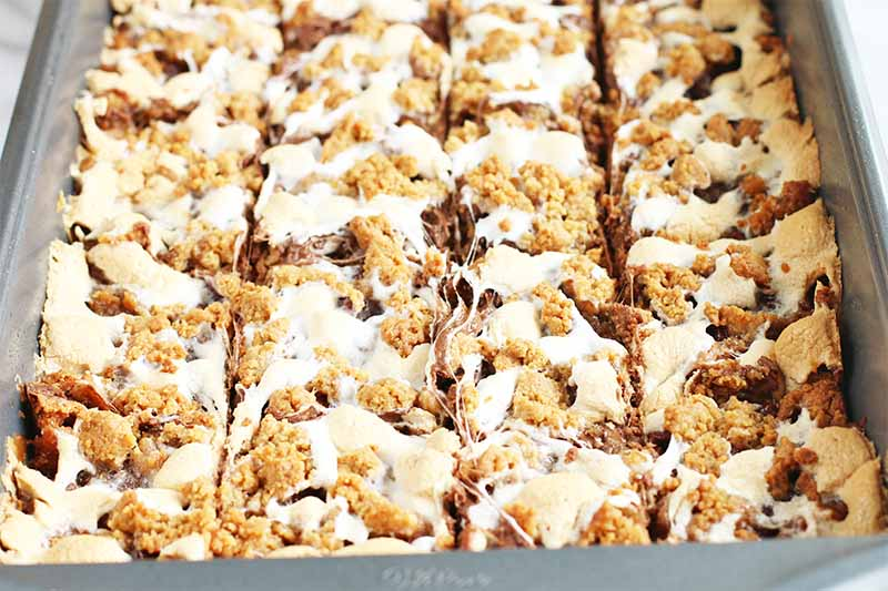 A gray metal baking tray filled with a mixture of graham cracker dough, melted marshmallow, and milk chocolate, sliced into four rows by four columns.