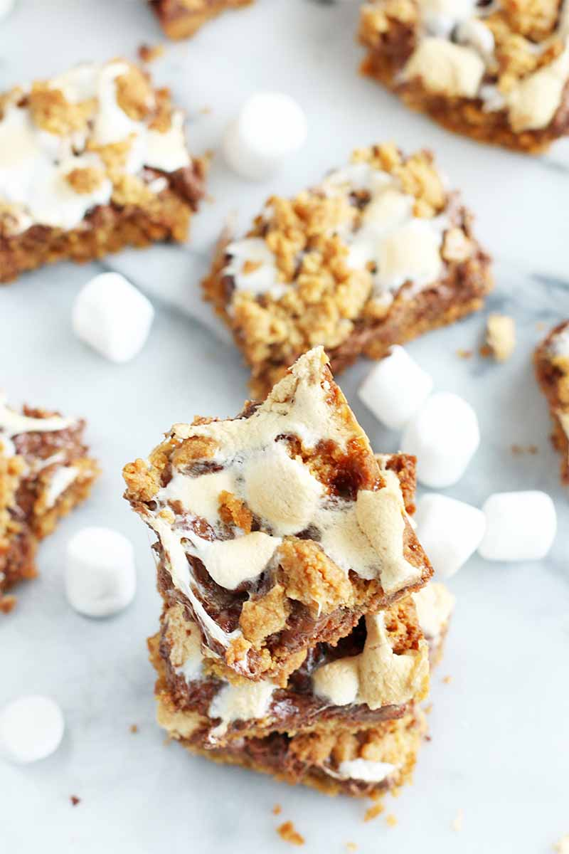 Oblique shot of a stack of three s'mores cookie bars with more scattered among miniature marshmallows on a gray and white marble surface.