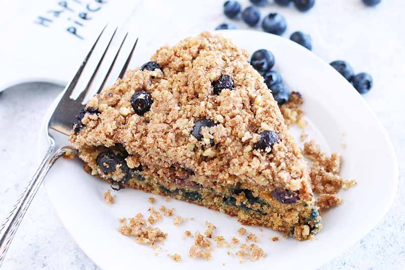 A slice of blueberry crumb cake with a fork and fresh berries.
