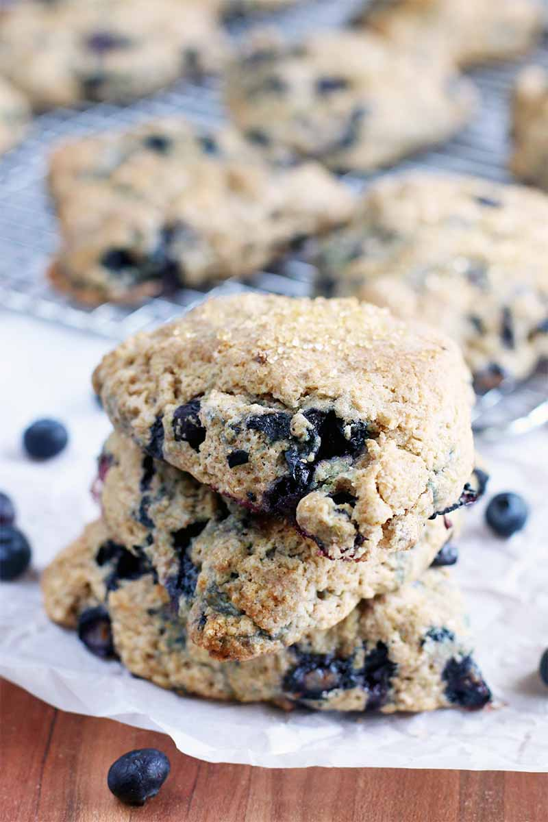 A stack of three scones on a piece of parchment paper with scattered blueberries on a brown wooden table, with a silver wire cooling rack topped with more of the breakfast items, fresh out of the oven.