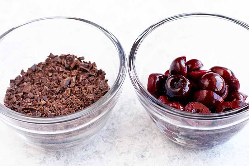 A glass bowl of chopped dark chocolate and a matching bowl of dark red cherries that have been cut in half, on a gray speckled white background.