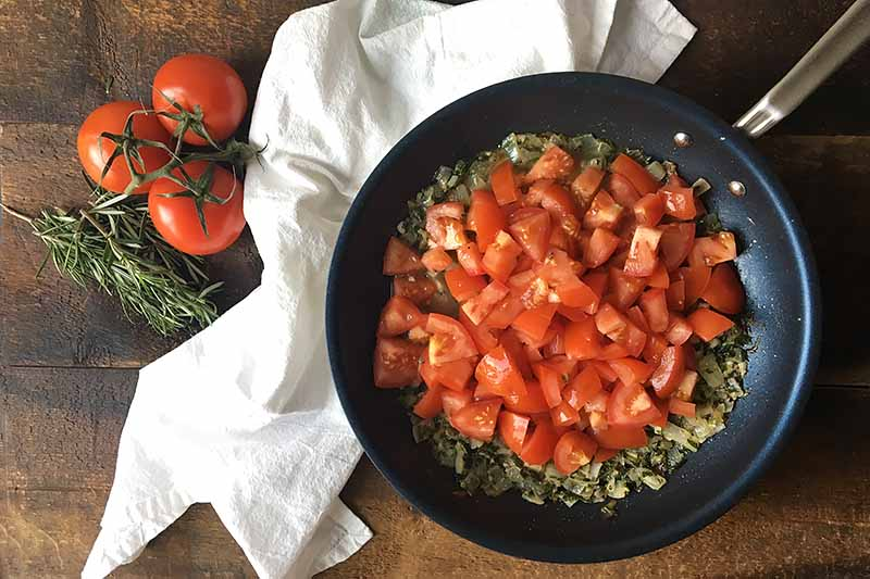 Horizontal image of a skillet filled with diced tomatoes on a white towel.