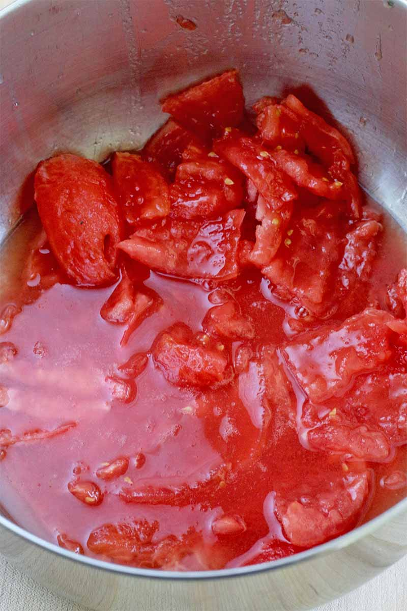 Closeup of peeled and chopped tomatoes and their juices, in a stock pot.