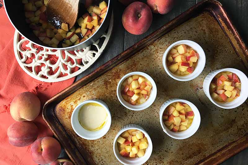 Horizontal image of ramekins filled with fruit on a baking sheet with a pot of fruit, an orange towel, and whole peaches.