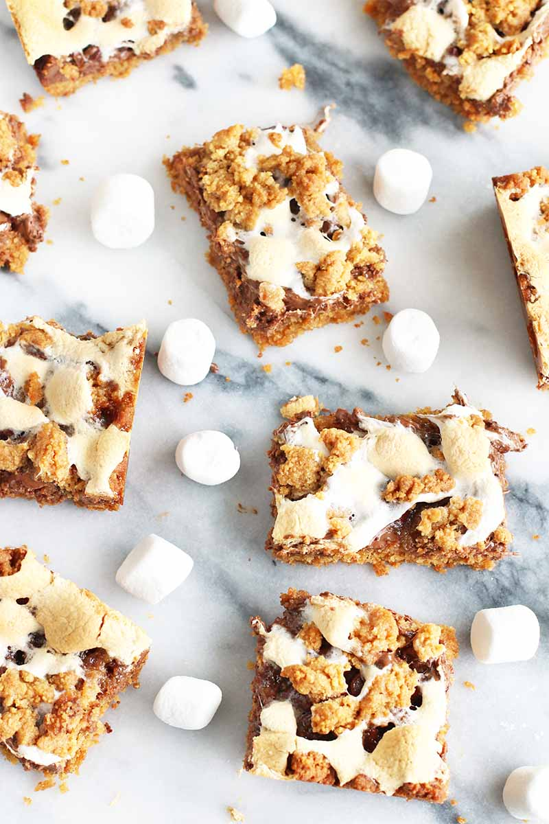 Top-down shot of s'mores dessert bars arranged haphazardly on a marble surface, with mini white marshmallows scattered in between.