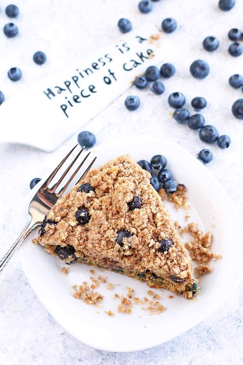 "A slice of blueberry coffee cake on a white plate with a fork, beside a white dessert server that says ""Happiness is a piece of cake"" on a white and blue speckled countertop with scattered fresh berries."
