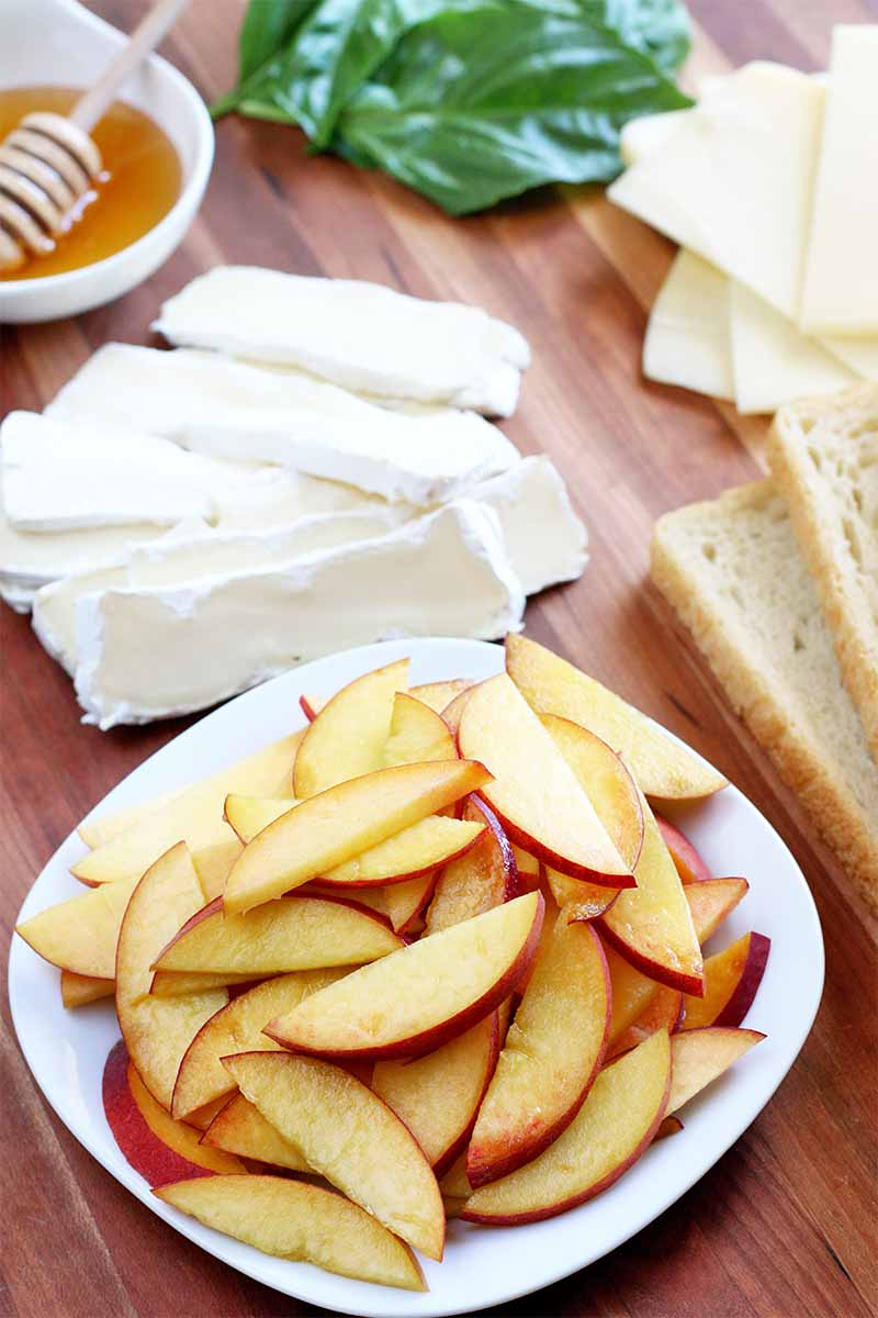 A plate of sliced peaches is in the foreground, with a plate of sliced cheese, a small bowl of honey with a wooden dipper, basil leaves, and two slices of bread in the background, on a brown wood surface.