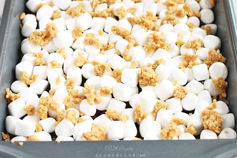 A bray baking pan filled with mini marshmallows, with graham cracker crumbs on top.
