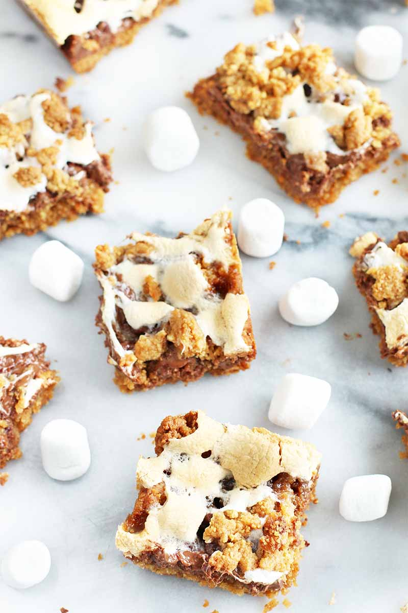 Vertical oblique view of s'mores cookie bars with scattered miniature marshmallows on a white and gray marble surface.