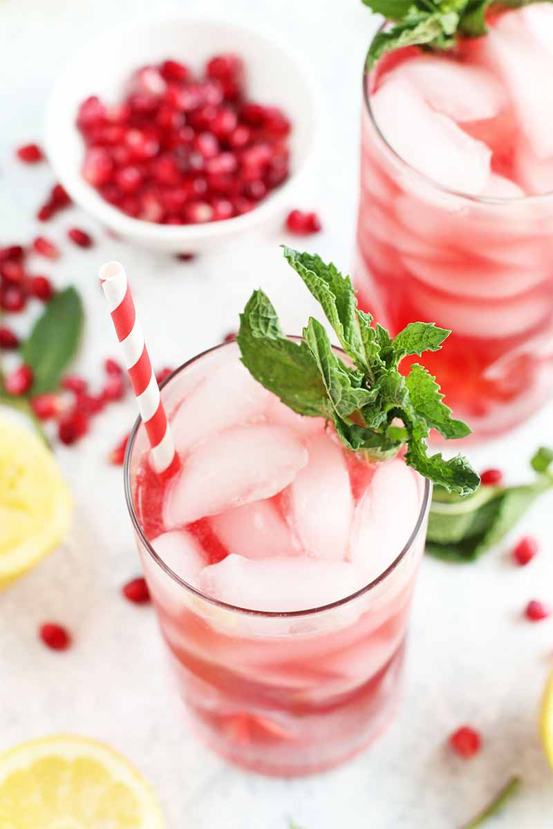 Vertical image of two glasses of pink lemonade shot at an oblique angle, on a white surface with a small bowl of pomegranate seeds and more scattered on the table with green mint leaves and yellow lemon slices.