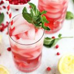 Two glasses of pink lemonade and ice with a red and white straw and a mint garnish, with more mint leaves, lemon slices, and pomegranate seeds scattered decoratively on a white background.