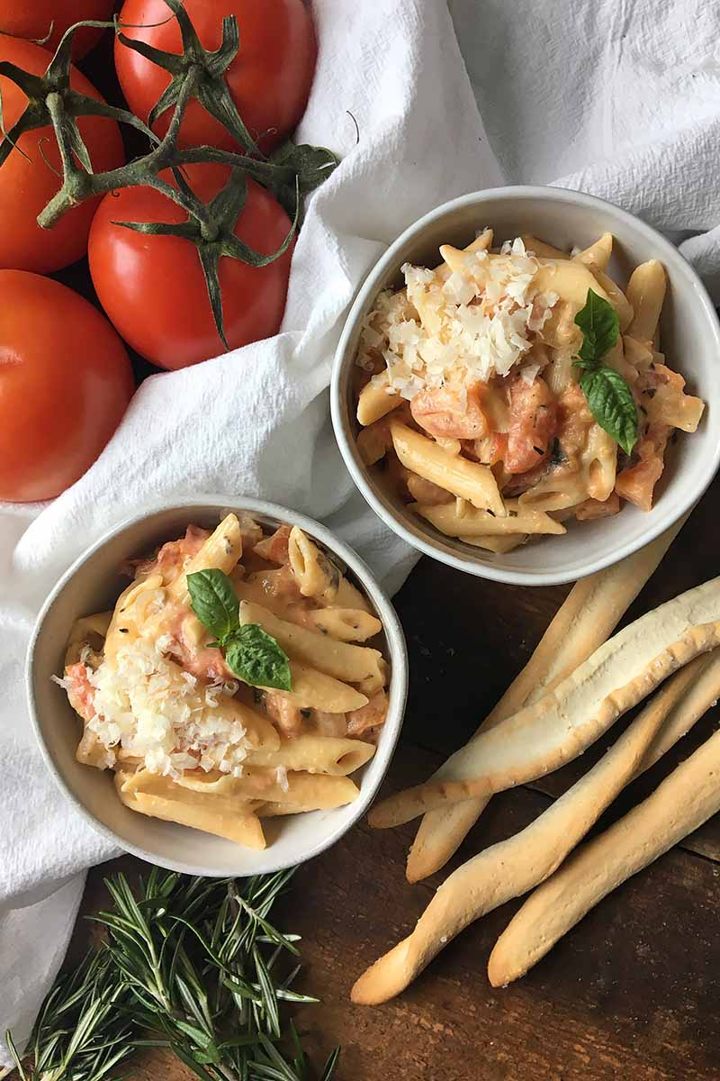 Vertical top-down image of two bowls with pasta and breadsticks on the side.