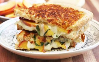 Two halves of a grilled cheese sandwich with peaches and basil stacked on top of each other on a white plate, with a plate of sliced fruit in the background, on a brown wooden cutting board.