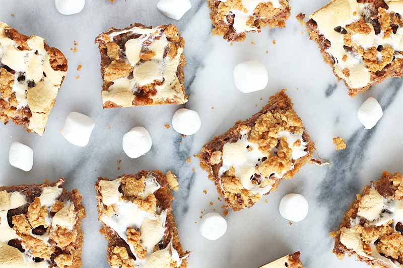 Top-down shot of marshmallow, chocolate, and graham cracker cookie bars, with scattered mini marshmallows on a gray and white marble surface.