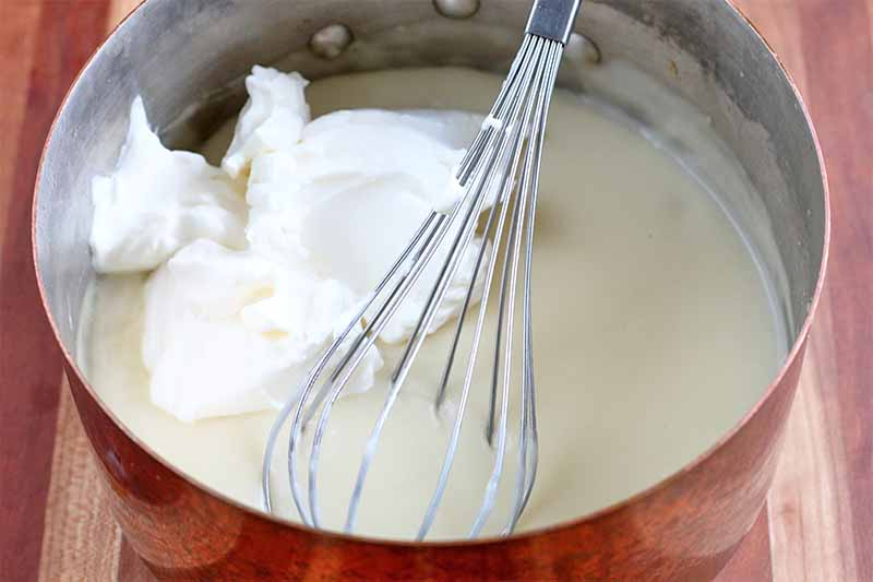 A large dollop of sour cream is is in a stainless steel mixing bowl with an off-white liquid mixture and a wire whisk, on a wood background.