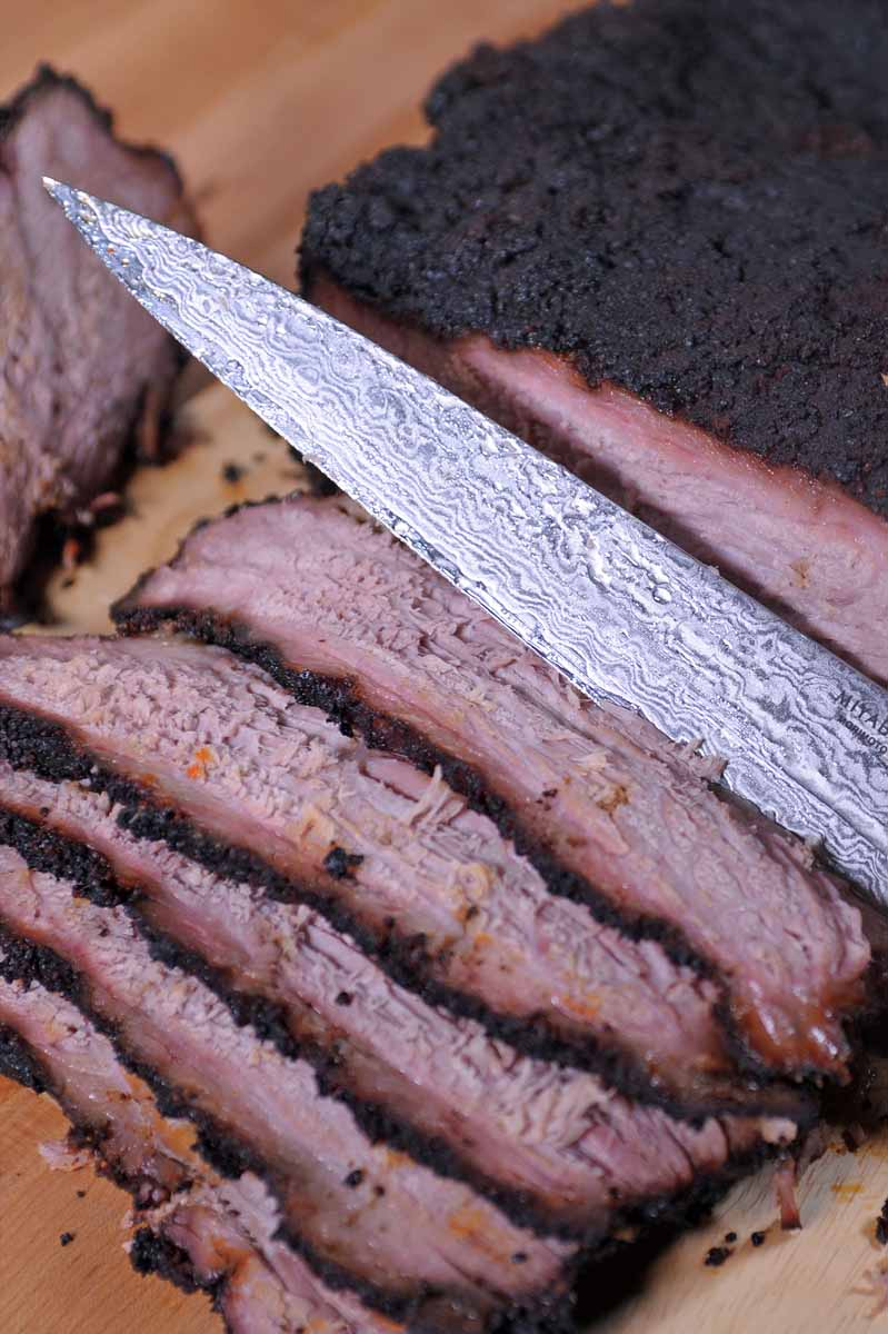 Closeup of a the blade of a Damascus-clad Japanese Sujihiki knife cutting slices off a brisket.