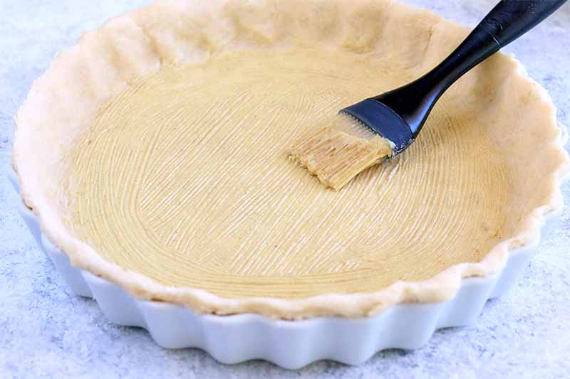 A scalloped white ceramic tart pan lined with a homemade crust and brushed with mustard, with a pastry brush, on a white and gray-blue speckled countertop.