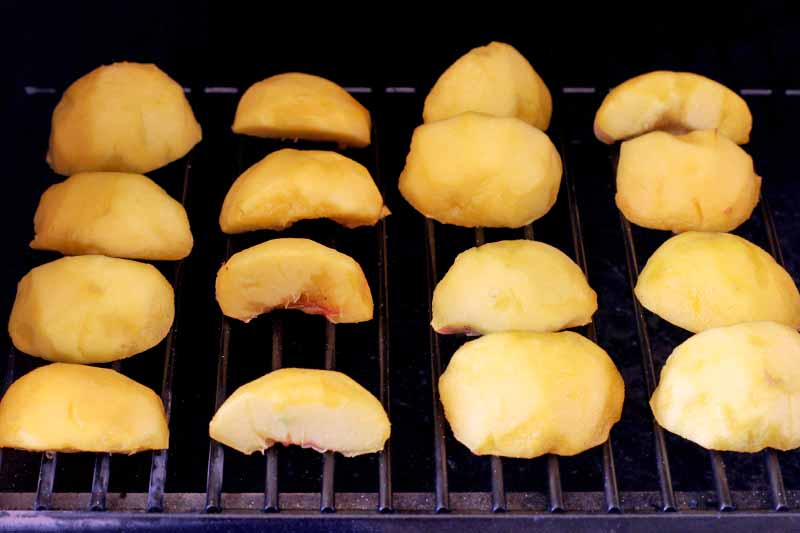 Peeled peach slices on a grill grate.
