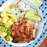 Top-down shot of a white bowl of grilled chicken, rice, pineapple, jalapeno, lime wedges, and fresh chopped herbs, on a dark and light blue patterned cloth, on top of a striped wood table.