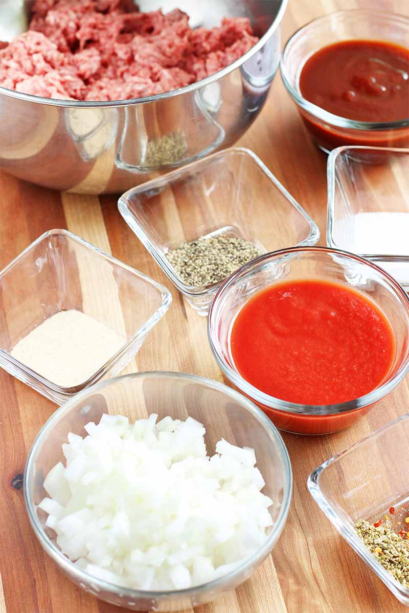 Small round and square bowls of red sauce, chopped white onions, spices, and a larger stainless steel bowl of raw ground beef, on a brown wood tabletop.