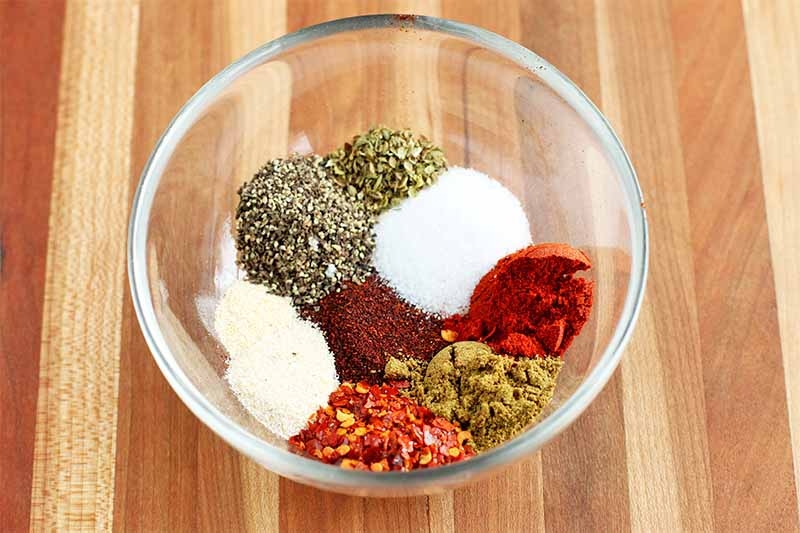 A clear glass dish of various individual spices that have not yet been mixed, including onion powder, garlic powder, red pepper flakes, black pepper, oregano, cumin, cayenne, paprika, and salt, on a wood background.