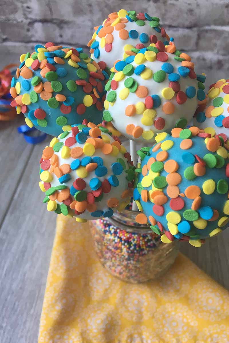 Vertical image of rainbow circle sprinkles covering assorted colored balls in a jar filled with more decorations.